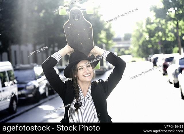 Woman wearing hat, holding skateboard over her head. Munich, Germany