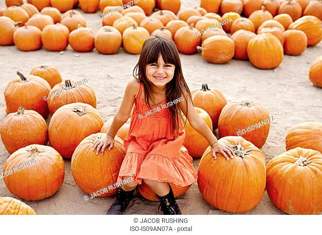 Portrait of girl sitting on pumpkin in farmyard