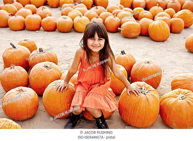 Portrait of girl sitting on pumpkin in farmyard