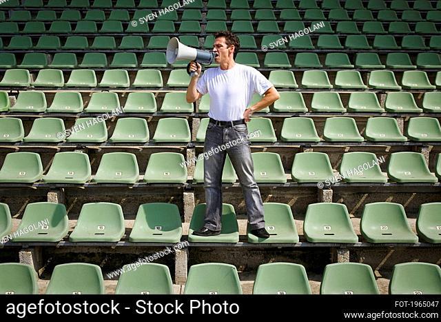 Man yelling into bullhorn on green stadium seats