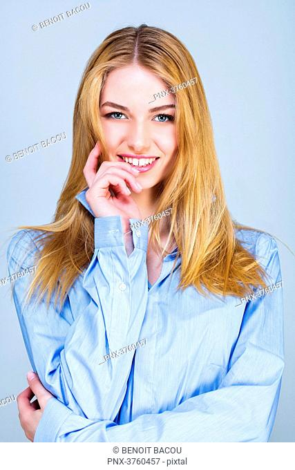 Portrait of a smiling young woman in shirt, hand on chin, looking toward the lens