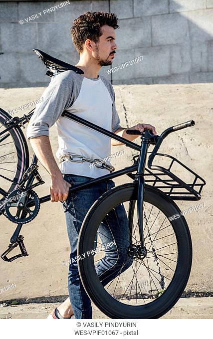 Young man carrying commuter fixie bike at concrete wall
