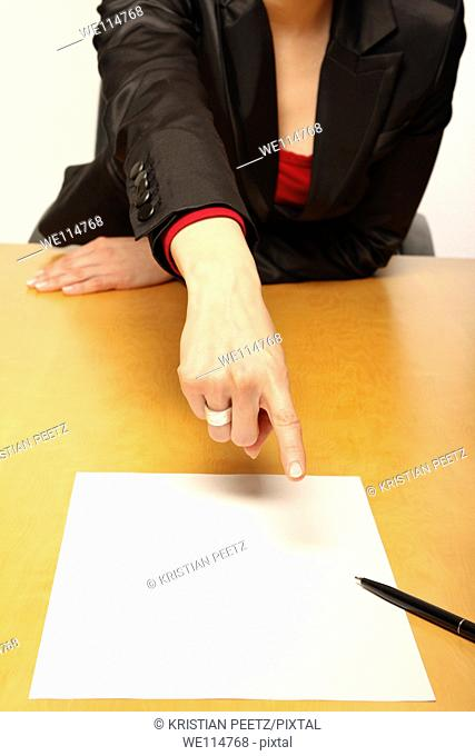 View of a business-woman sitting at the desk infront of blank paper and gesturing