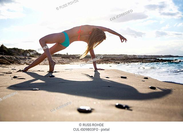 Young woman on beach, in yoga position, rear view