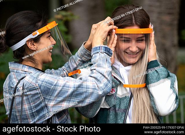 25 May 2020, North Rhine-Westphalia, Cologne: Schoolgirl Rosa (l) helps her friend Gizem put on a face shield during a press appointment
