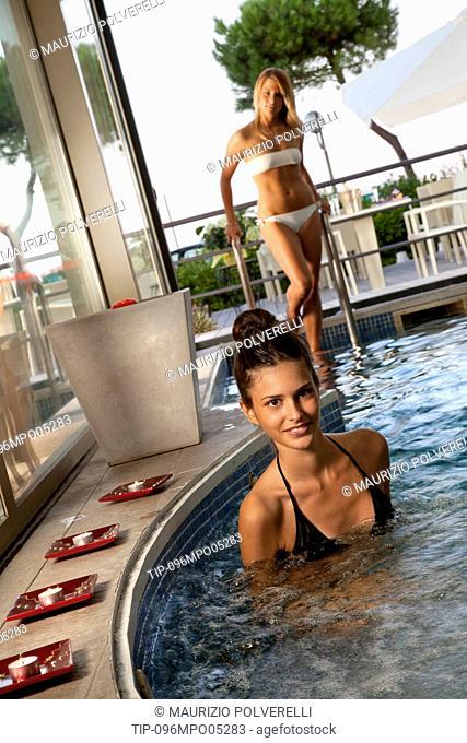 Two young women in indoor pool