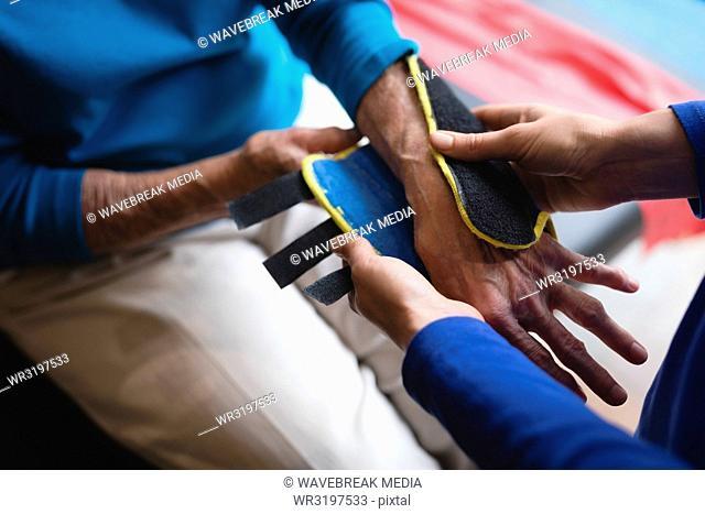 Physiotherapist putting on a wrist support brace on senior woman