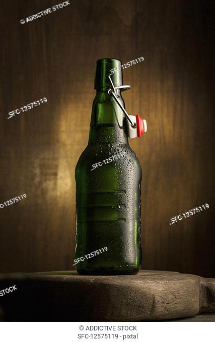 An open bottle of beer on a wooden board