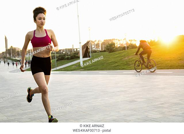 Young woman jogging at evening twilight