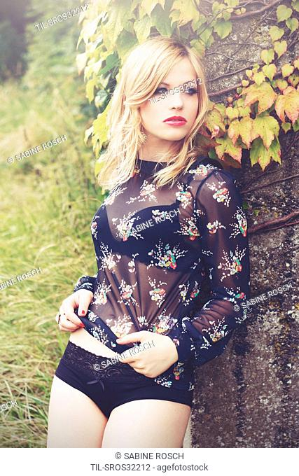 young woman standing outdoor in the nature with blonde hair turning her face to the side .wearing a black underwear