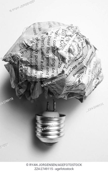 Scrunched up words inspiring innovation with a inventive lightbulb metaphor. Contextual paper bulbs