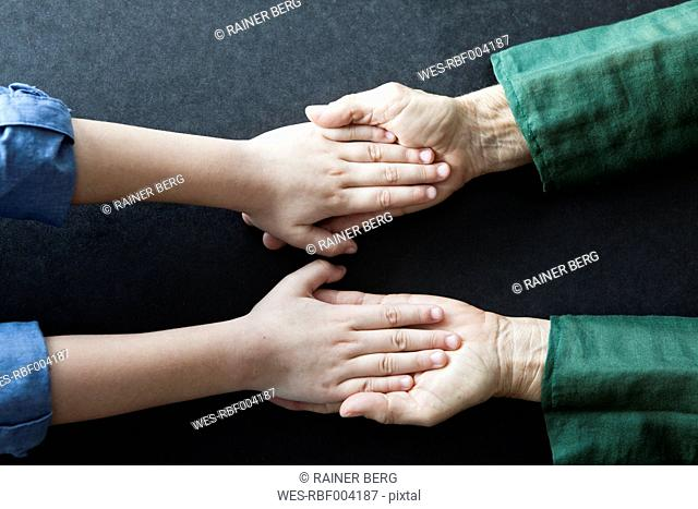 Grandmother and granddaughter holding hands, close-up