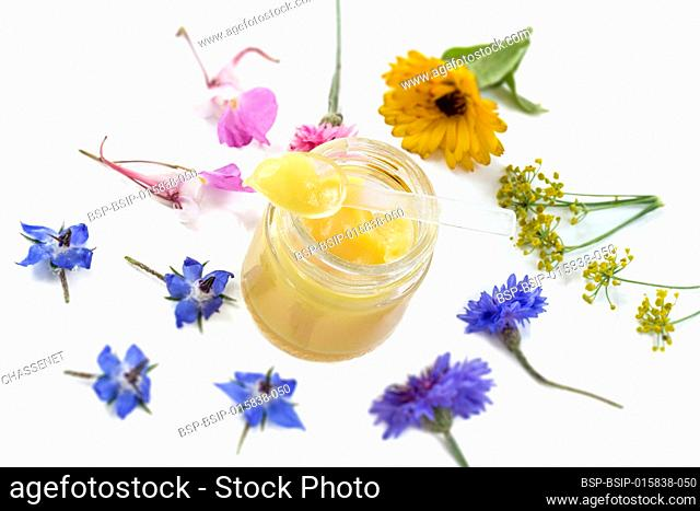 Raw organic royal jelly in a small bottle with litte spoon on small bottle surrounded by flowers on white background