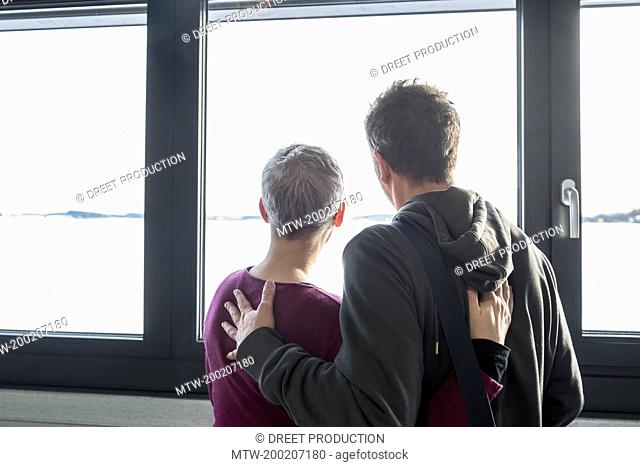 Rear view of couple looking out of window, Bavaria, Germany