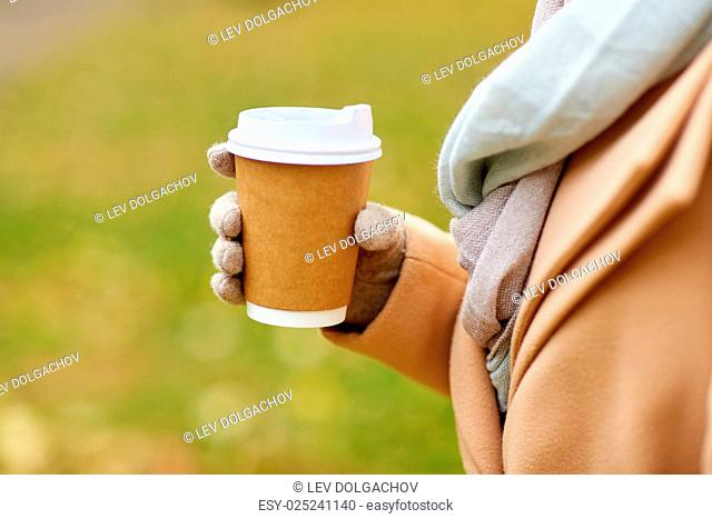 season, hot drinks, advertisement and people concept - close up of woman with coffee or tea disposable paper cup in autumn park