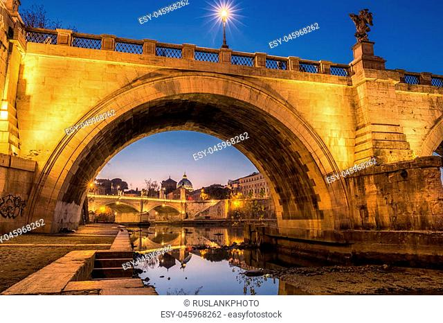 Blue hour view of St. Peters Basilica in the Vatican and the Ponte Sant'Angelo, Bridge of Angels, at the Castel Sant'Angelo and river Tiber in Rome, Italy
