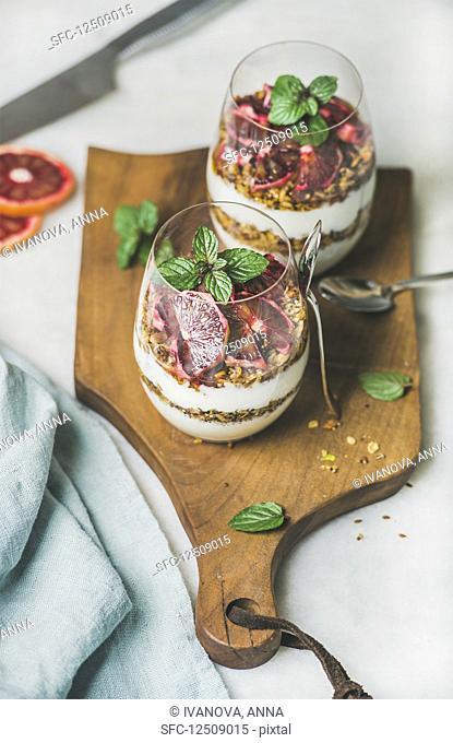 Greek yogurt, granola, blood orange layered parfait in glasses with mint leaves