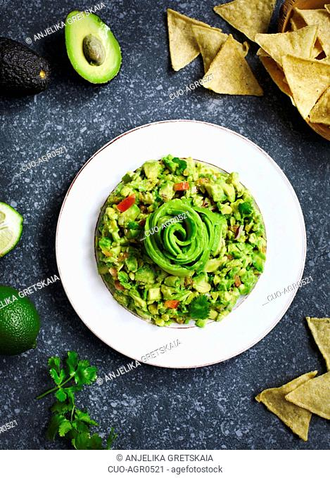 Guacamole and tortilla chips on stone background
