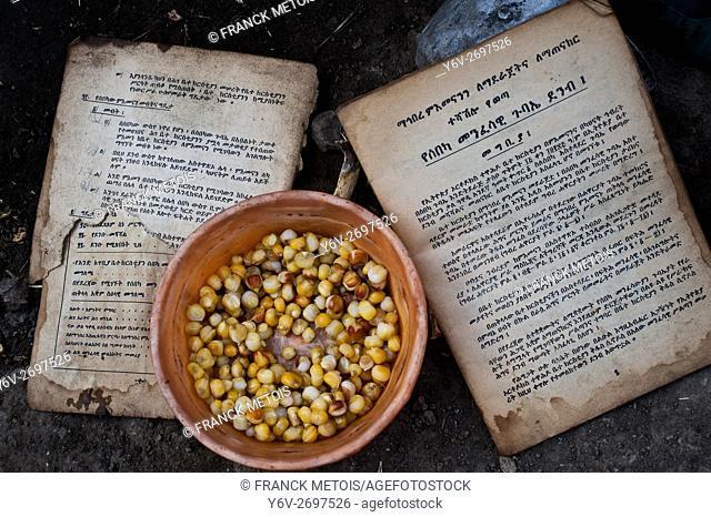 Orthodox christian book + morning meal ( i. e. corn grains). Photo taken outside the hut of a blacksmith family living near Korem ( Tigray state, Ethiopia)
