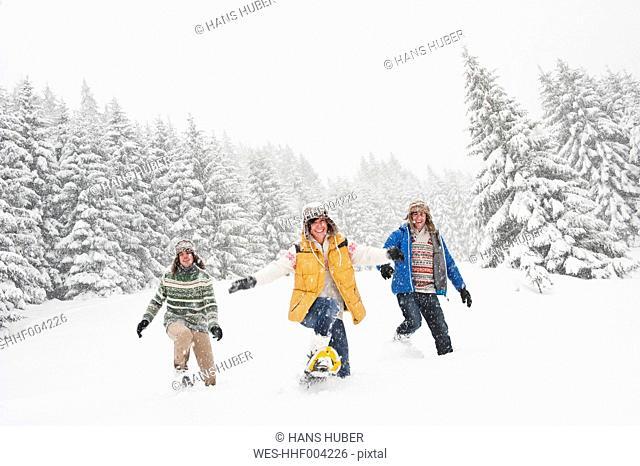 Austria, Salzburg, Men and woman walking through winter landscape