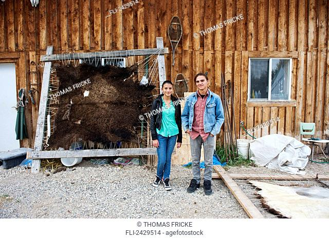 Native American teenaged boy and girl standing in front of a stretched buffalo hide; Rossburn, Manitoba, Canada