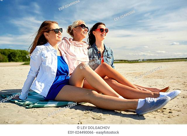 summer vacation, holidays, travel and people concept - group of smiling young women in sunglasses and casual clothes on sunbathing on beach blanket