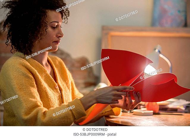 Woman folding red cardboard