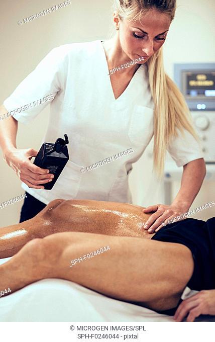 Sports massage. Physical therapist massaging man, applying massage oil
