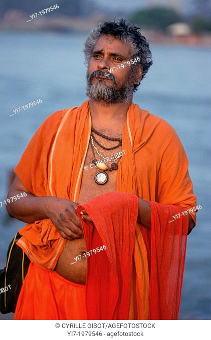 India, Haridwar, Hindu pilgrim standing by the Ganges river