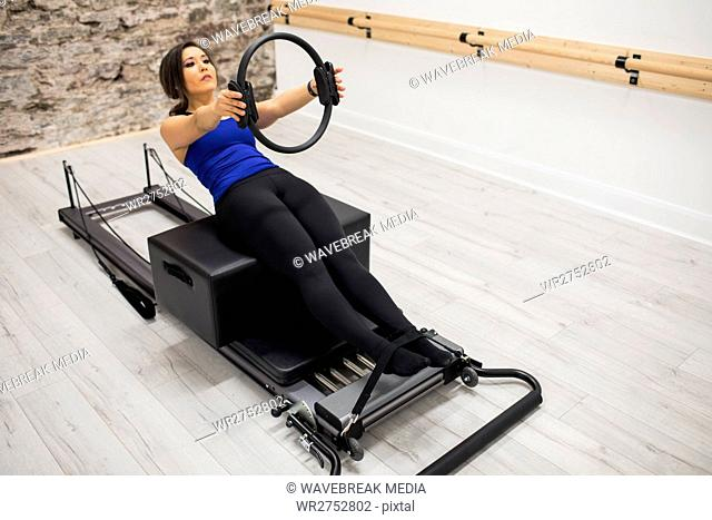 Woman exercising with pilates ring