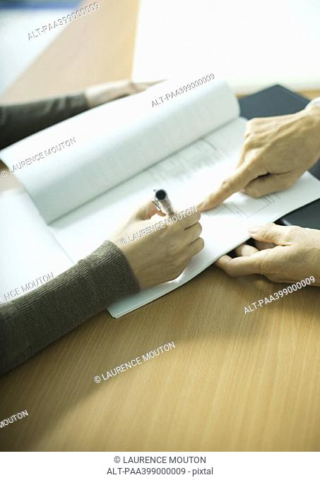 Woman signing contract, close-up of hands