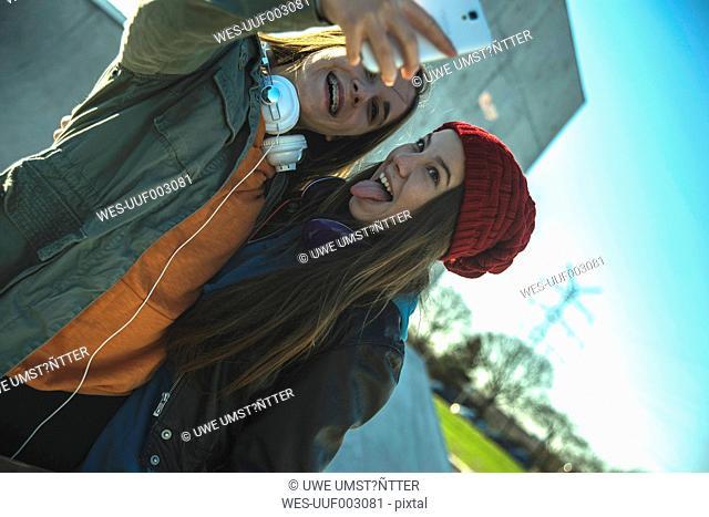 Two playful teenage girls outdoors taking selfie