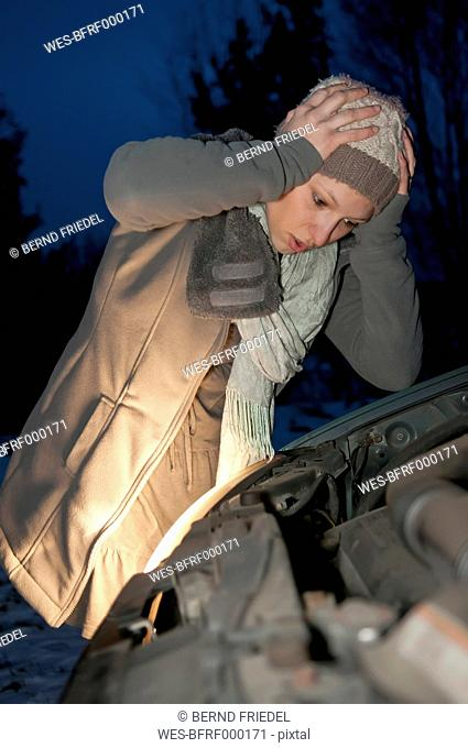 Germany, Brandenburg, Shocked young woman with car breaks down at night