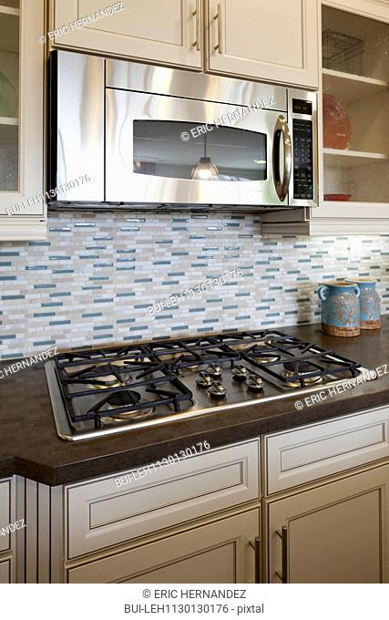 Microwave and gas stove in kitchen