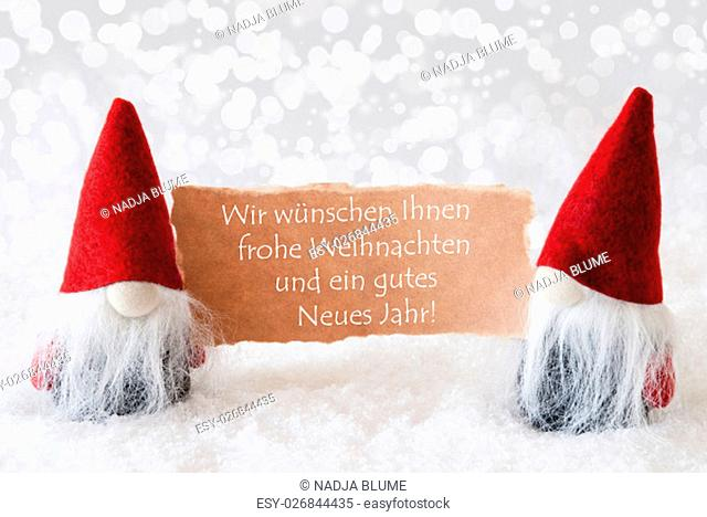 Christmas Greeting Card With Two Red Gnomes. Sparkling Bokeh Background With Snow. German Text Frohe Weihnachten Und Ein Gutes Neues Jahr Means Merry Christmas...