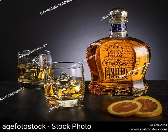 Whiskey and 2 glasses on wooden black background