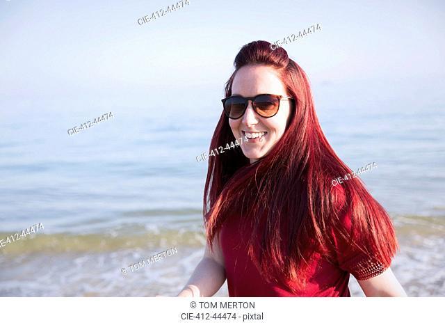 Portrait smiling, confident woman on sunny ocean beach
