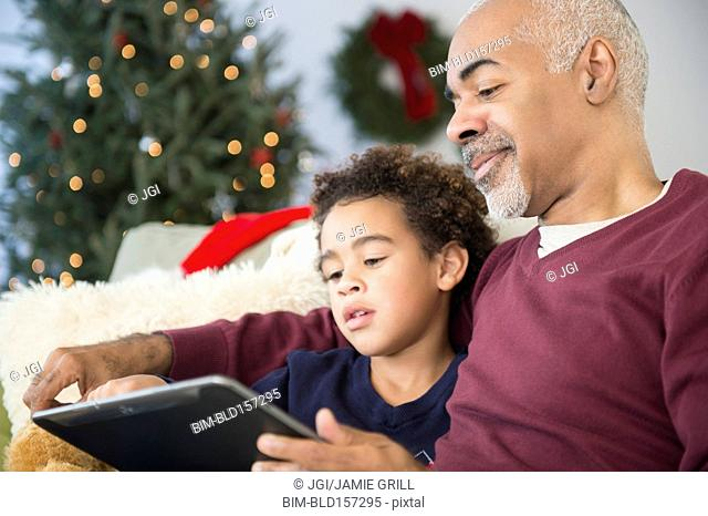 Mixed race grandfather and grandson using digital tablet at Christmas