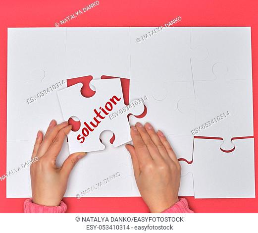 female hand holding white puzzle with the word solution, process of closing the missing element , conceptual business background