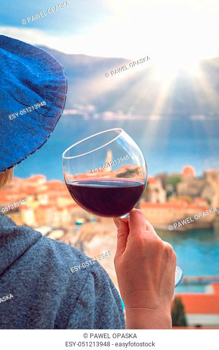 Caucasian woman wearing blue hat standing in an apartment balcony and holding glass with red wine looking at the Budva town below, Montenegro