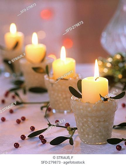 Four Advent candles White pillar candles with mistletoe, beads