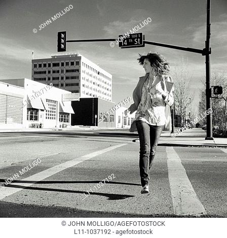 Young woman, running across empty downtown street