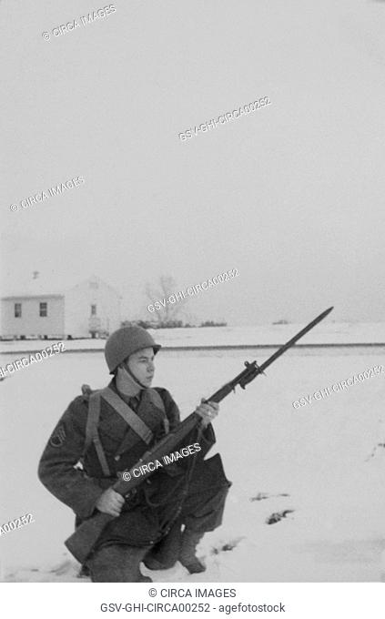 Military Soldier in Uniform Kneeling in Snow with Rifle & Bayonet, Portrait, WWII, HQ 2nd Battalion, 389th Infantry, US Army Military Base, Indiana, USA, 1942