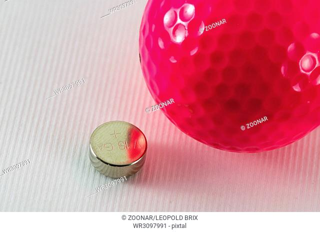 coin cell and pink coloured golf ball