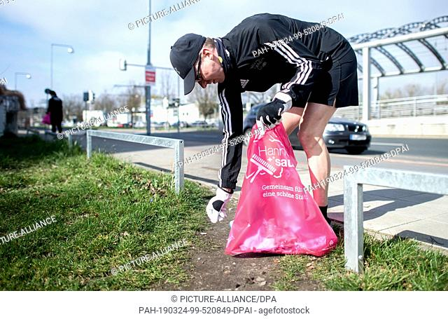24 March 2019, Lower Saxony, Hannover: Jogger Oliver collects garbage lying on the ground around the Noltemeyer Bridge in the Bothfeld district with gloves and...