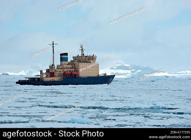 icebreaker which floats on the frozen Strait spring Antarctic mountains in the background