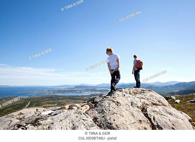 Boy and father looking out from rock formation over landscape, Aure, More og Romsdal, Norway
