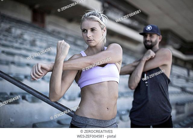 Portrait of sportswoman doing stretching exercies on grandstand of a stadium