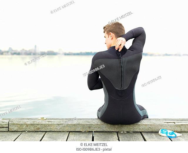 Rear view of man in wetsuit sitting on pier, Melbourne, Victoria, Australia, Oceania