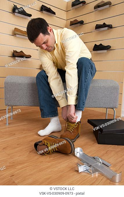 USA, Illinois, Metamora, Man trying on hiking boots in store